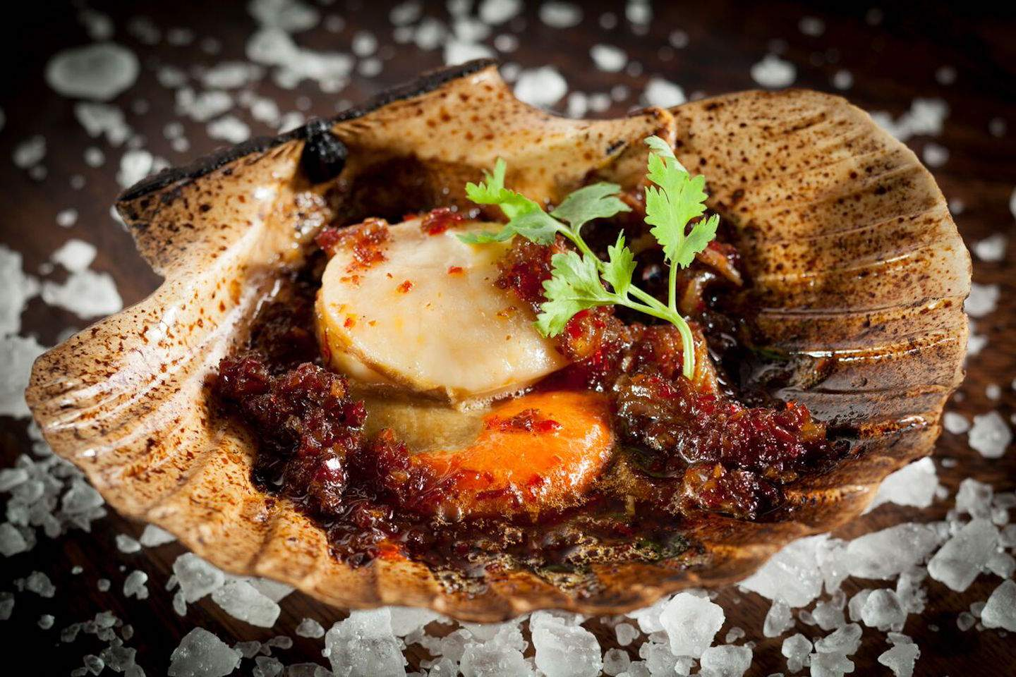 A grilled scallop dish from Burnt Ends. The restaurant has chosen to do away with prawns on its menu as prawn-farming is increasingly associated with the destruction of mangrove areas, coastal pollution, salinisation, and other detriments to the environment.