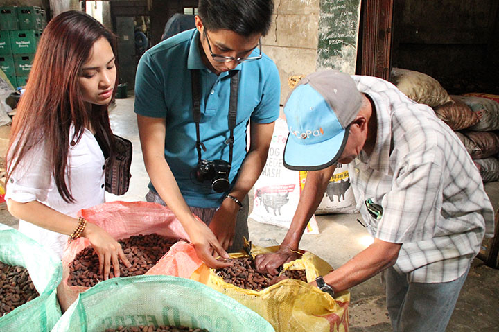 Arvin Peralta (in blue) inspects the cocoa beans with a farmer.