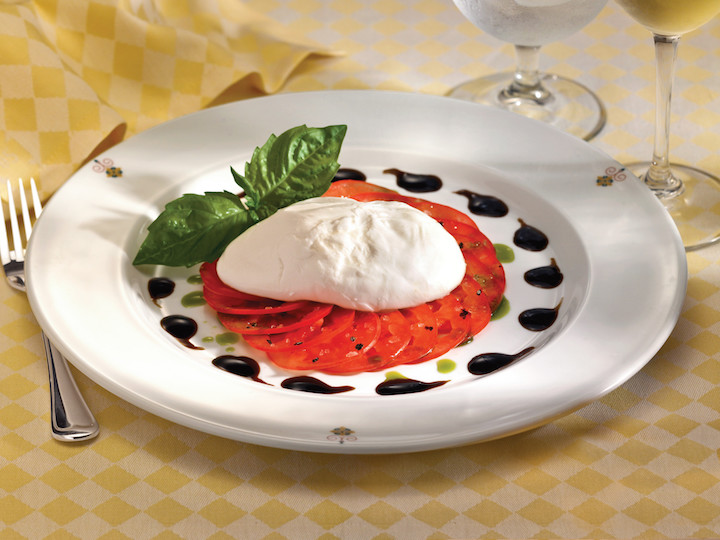 A light salad of fresh mozzarella and tomatoes dressed in tangy balsamic vinegar is a refreshing choice for a warm day.