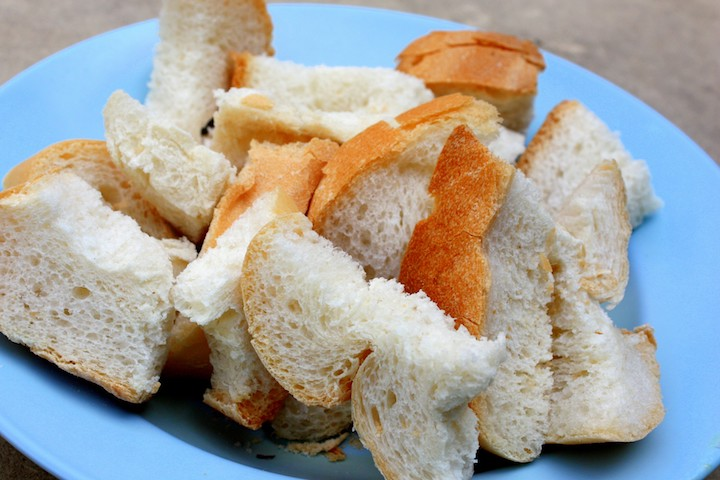 A fluffy loaf of white bread often accompanies a serving of kambing soup
